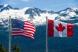 Canadian and American flags in the mountains